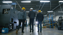 3 men tour a warehouse wearing hardhats